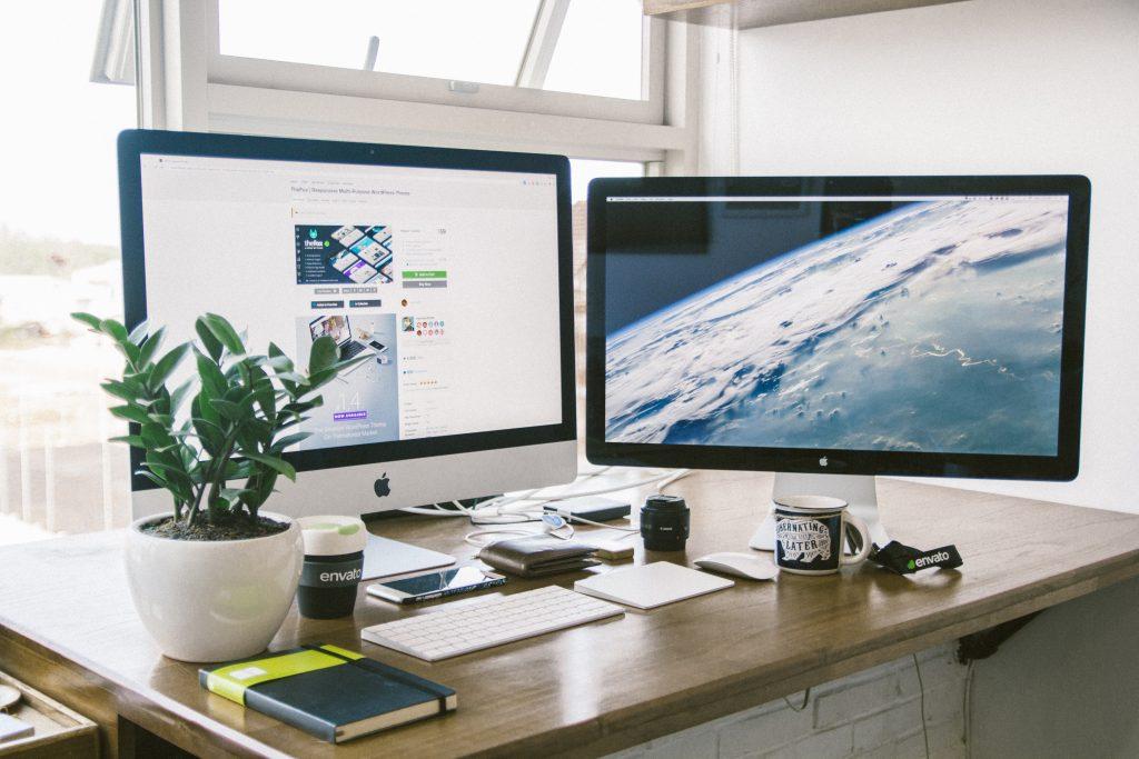 Tietokone kahdella näytöllä elegantisti sovitellussa kuvassa